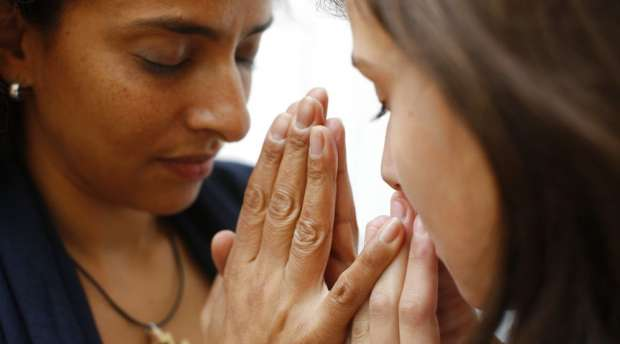 Mother and daughter praying at