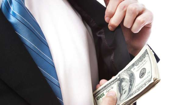 Business Man putting a wad of cash in his suit jacket pocket on white